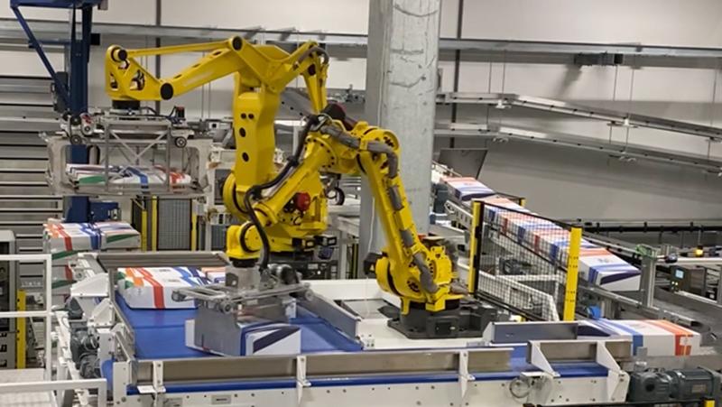 Le robot palettiseur, combiné à un robot qui forme une couche complète de produits